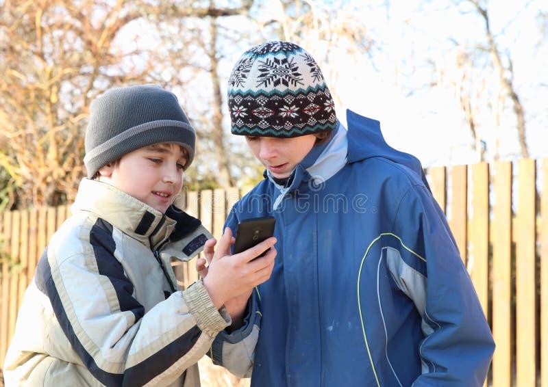 Мальчики играя с телефоном mobil стоковое изображение