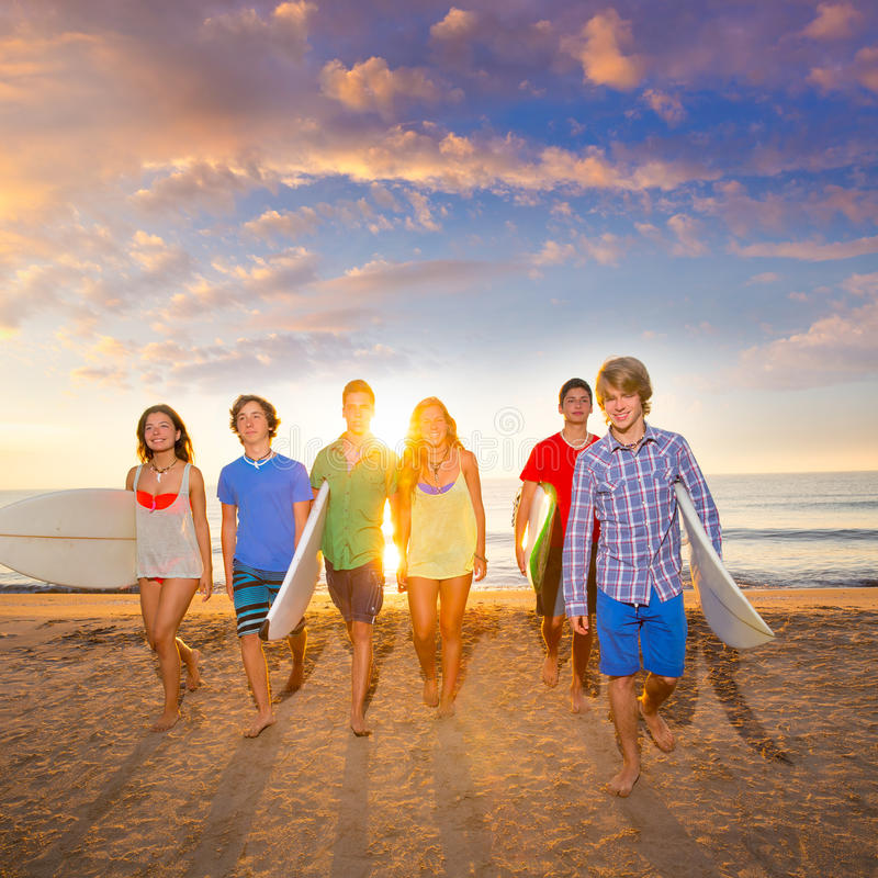 Мальчики и девушки серферов собирают идти на пляж стоковое фото rf