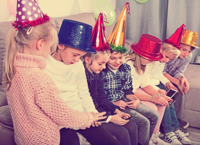 Мальчики и девушки тратя время играя с smartphones стоковая фотография rf