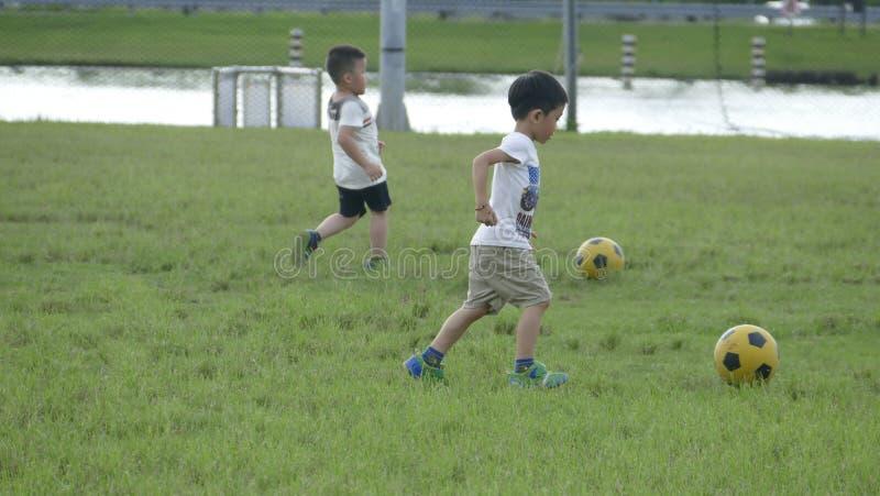 Мальчики пиная футбол на спортивной площадке стоковое фото