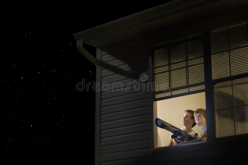 Мальчики при телескоп смотря ночное небо стоковое фото
