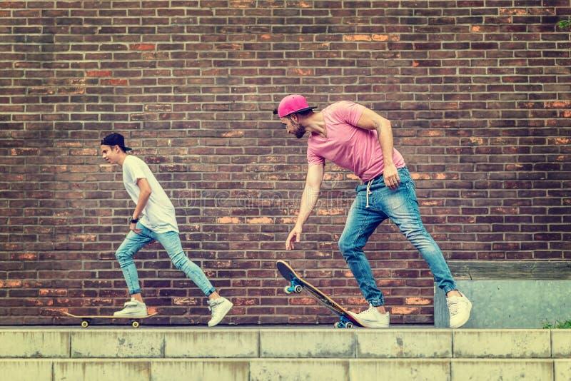 Мальчики скейтбордиста кирпичной стеной стоковое фото