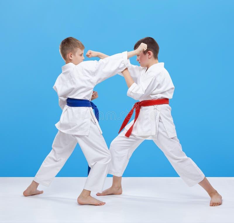 Мальчики тренируют дуновения и блоки карате на голубой предпосылке стоковые изображения rf
