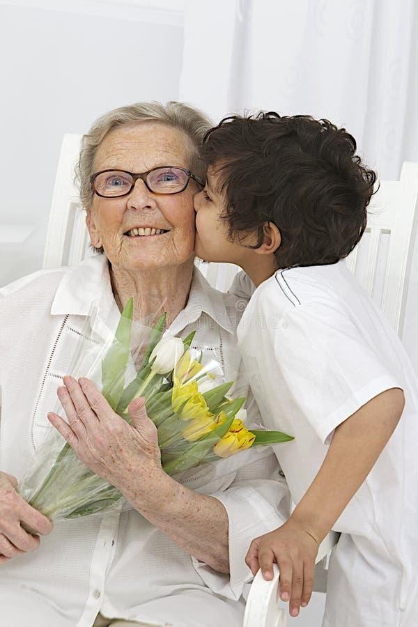 Мальчик давая цветки к его бабушке стоковая фотография rf