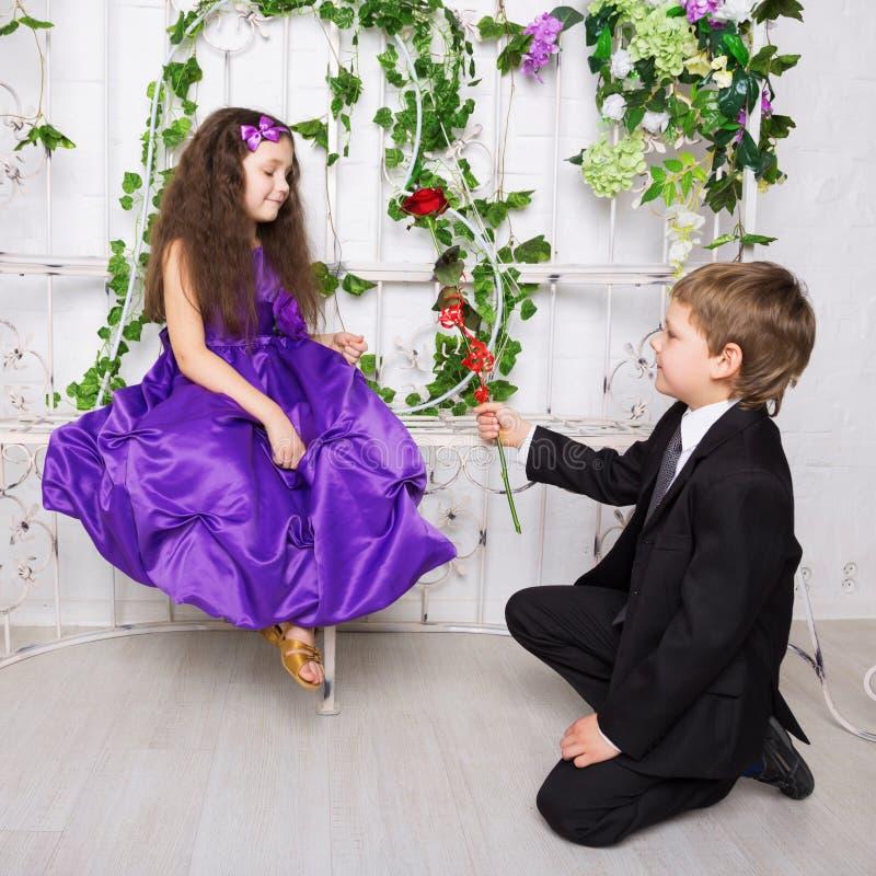 Мальчик дает розу к девушке Влюбленность детей стоковое фото
