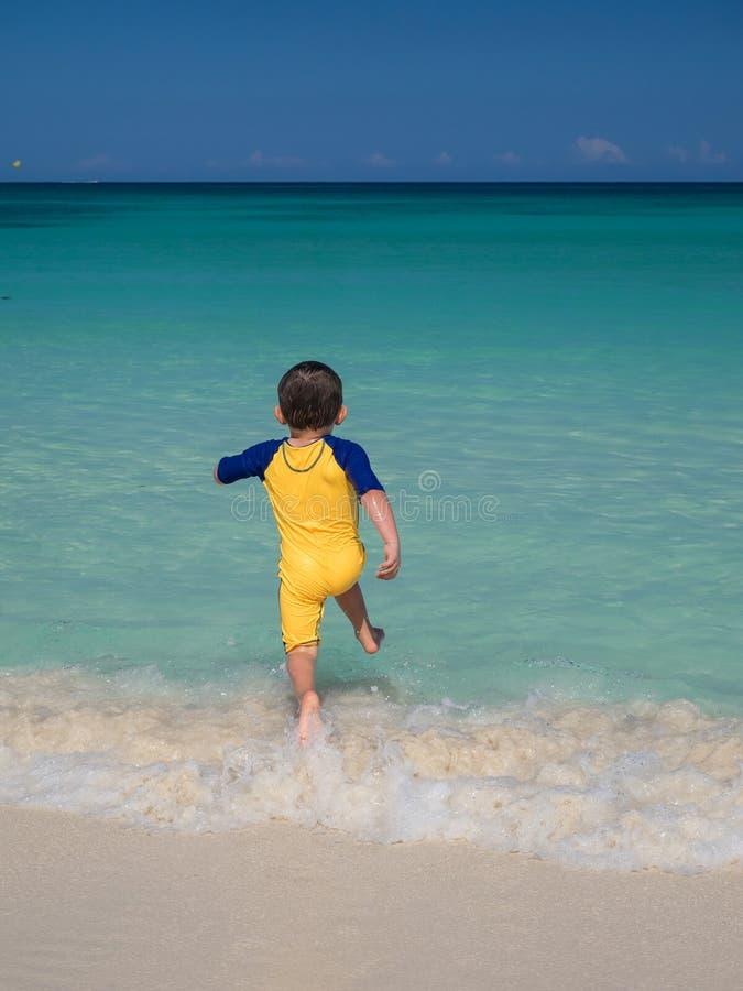Мальчик бежать в океан стоковое фото rf