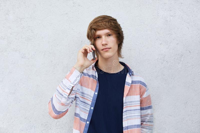Мальчик битника при темные глаза и стильный стиль причёсок имея серьезное выражение вызывая его мать над умным телефоном изолиров стоковая фотография