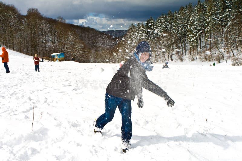 Мальчик бросает снежный ком в зимнем ландшафте стоковая фотография rf