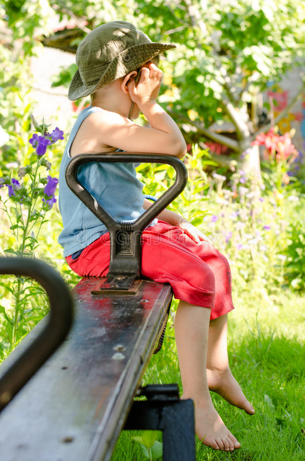 Мальчик быть в дурном настроении по мере того как он сидит на seesaw стоковая фотография rf