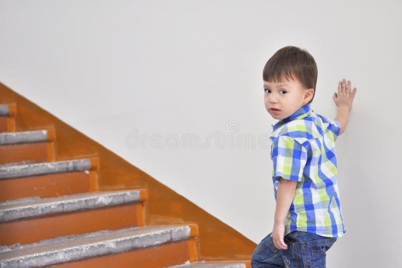 Мальчик взбирается вверх лестницы стоковая фотография rf