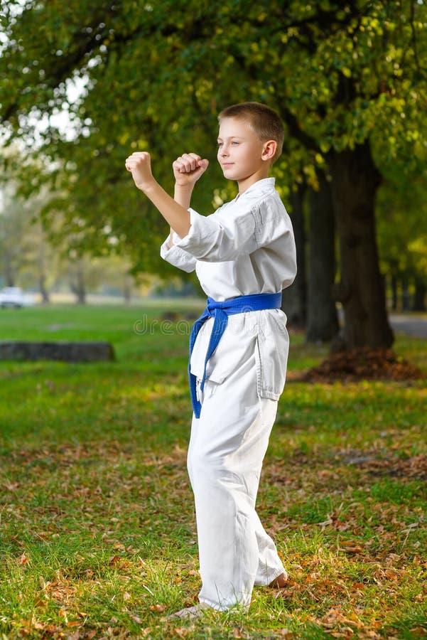 Мальчик в белом кимоно во время карате тренировки стоковые фото