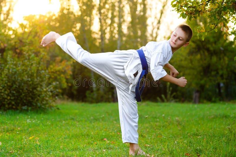 Мальчик в белом кимоно во время карате тренировки стоковое изображение rf