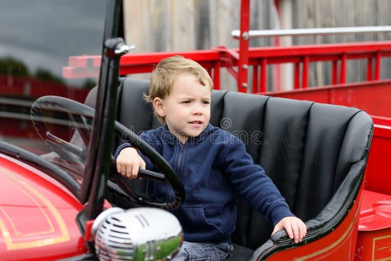 Мальчик в винтажной пожарной машине стоковые фото