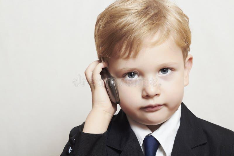 Мальчик в деловом костюме с сотовым телефоном. красивый ребенок. модный ребенк стоковая фотография rf