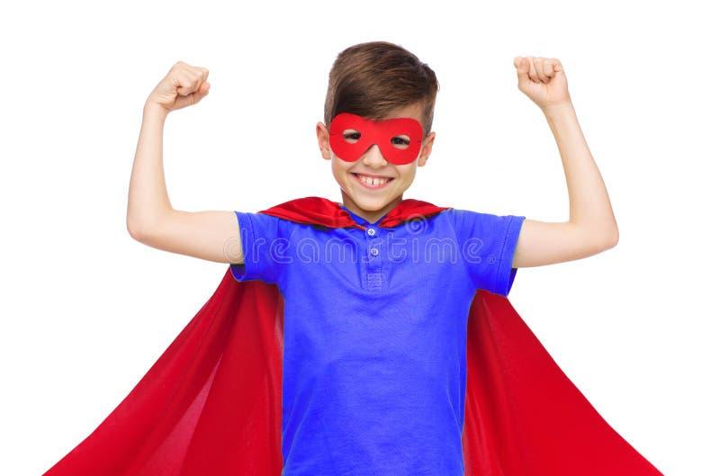 Мальчик в красной накидке супергероя и маска показывая кулаки стоковое изображение