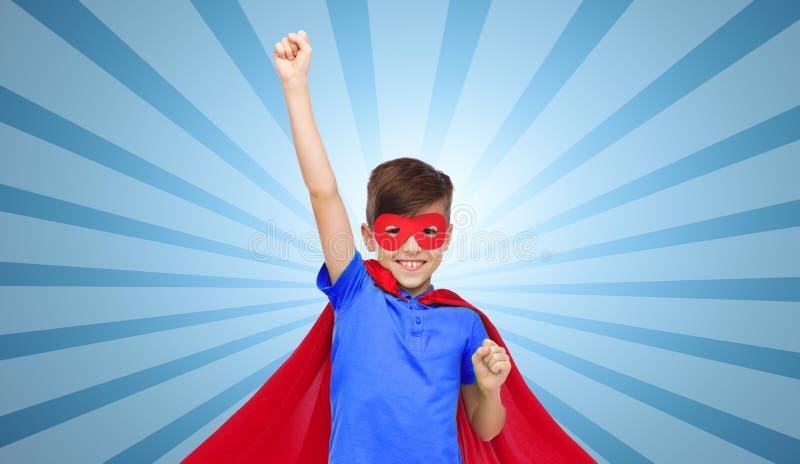 Мальчик в красной накидке супергероя и маска показывая кулаки стоковые изображения