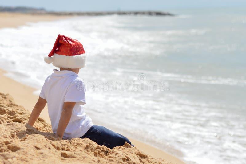 Мальчик в красной шляпе Санты смотря океанские волны стоковые изображения