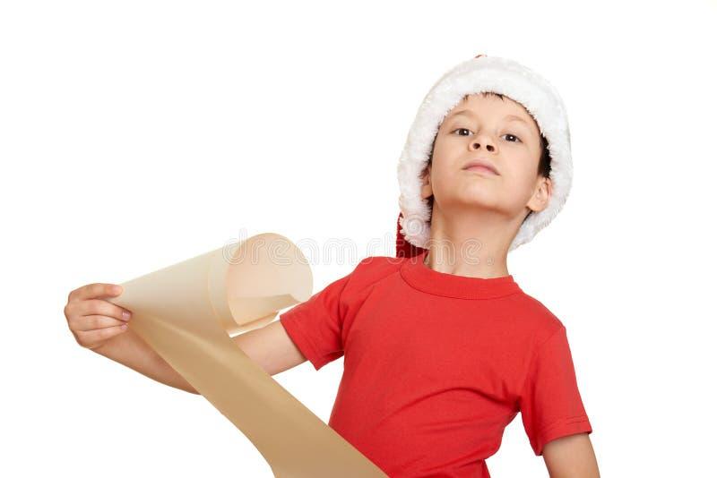 Мальчик в красной шляпе с длинным переченем желает к santa - концепции рождества зимнего отдыха стоковая фотография
