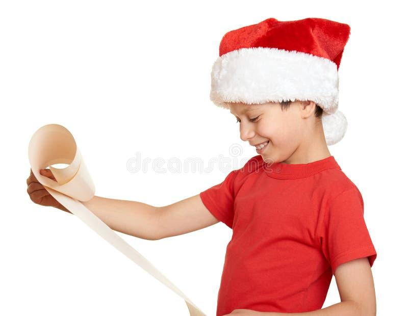 Мальчик в красной шляпе с длинным переченем желает к santa - концепции рождества зимнего отдыха стоковое изображение