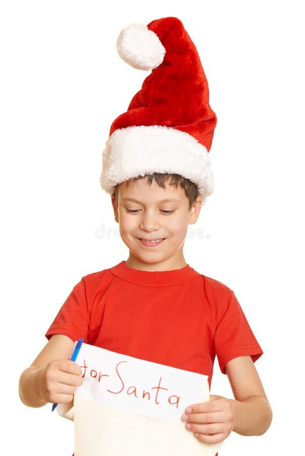 Мальчик в красной шляпе с длинным переченем желает к santa - концепции рождества зимнего отдыха стоковые изображения