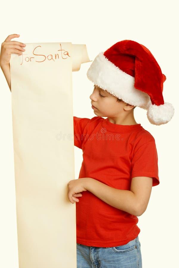 Мальчик в красной шляпе с длинным переченем желает к santa - концепция рождества зимнего отдыха, желтеет тонизированный стоковое фото rf