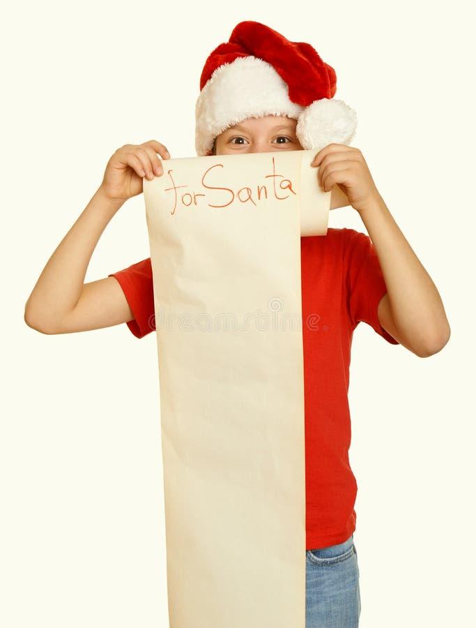 Мальчик в красной шляпе с длинным переченем желает к santa - концепция рождества зимнего отдыха, желтеет тонизированный стоковые фото