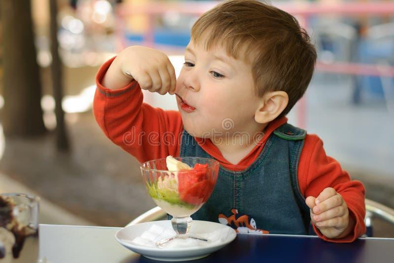 Мальчик в красном hoodie ест мороженое стоковые фото