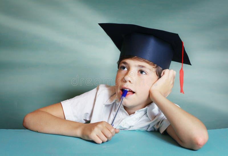 Мальчик в крышке градации думает о вопросе школы стоковое изображение