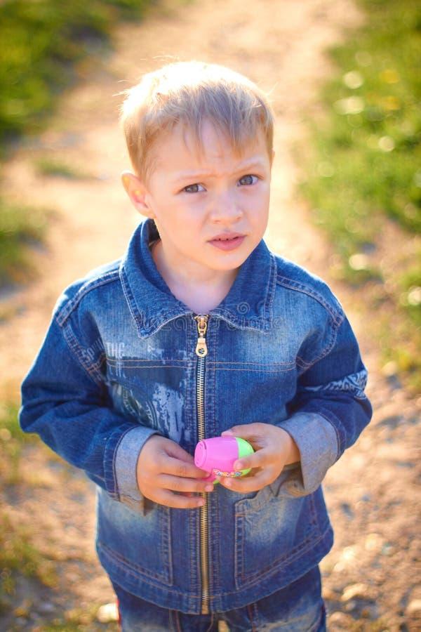 Мальчик в крышке играя outdoors в лете на солнечный теплый день, траве, зеленых цветах, природе стоковое фото