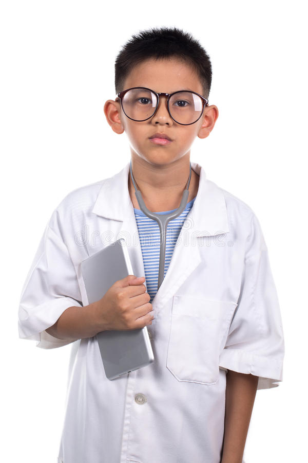 Мальчик в медицинской равномерной держа таблетке стоковые изображения