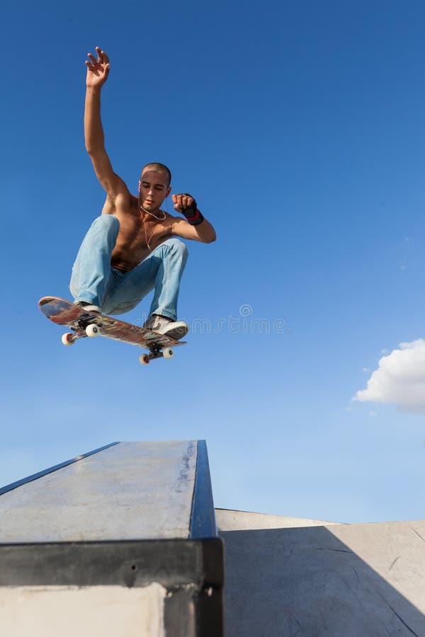 Мальчик в скачке на скейтборде стоковые фото