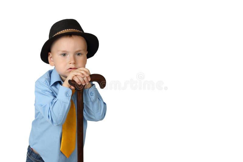 Мальчик в черной шляпе с тросточкой стоковое изображение