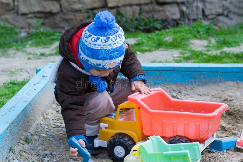 Мальчик в ящике с песком играя с автомобилем стоковое изображение rf
