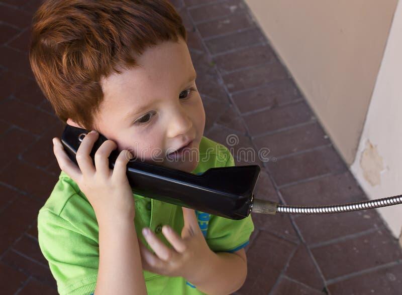 Мальчик говоря на общественном телефоне стоковое изображение rf