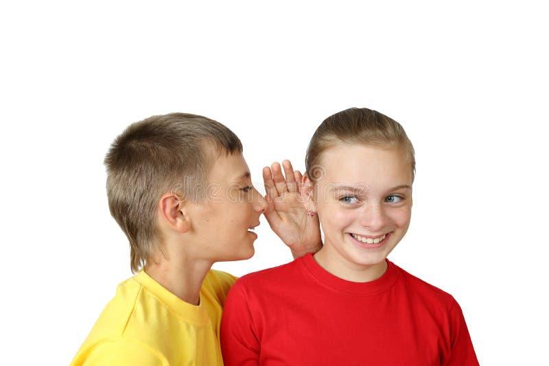 Мальчик говоря секрет к девушке стоковые изображения rf