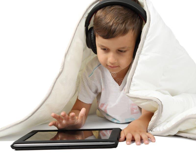 Мальчик лежа под одеялом с таблеткой в наушниках стоковая фотография