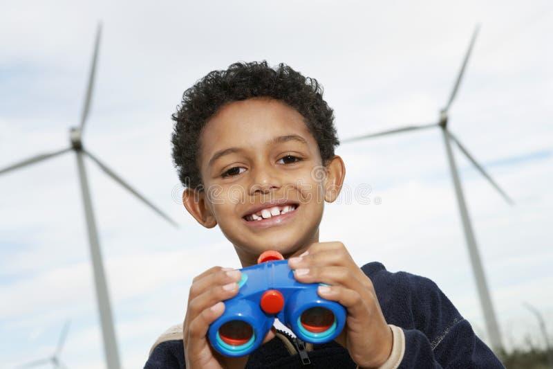 Мальчик держа бинокли на ветровой электростанции стоковое изображение