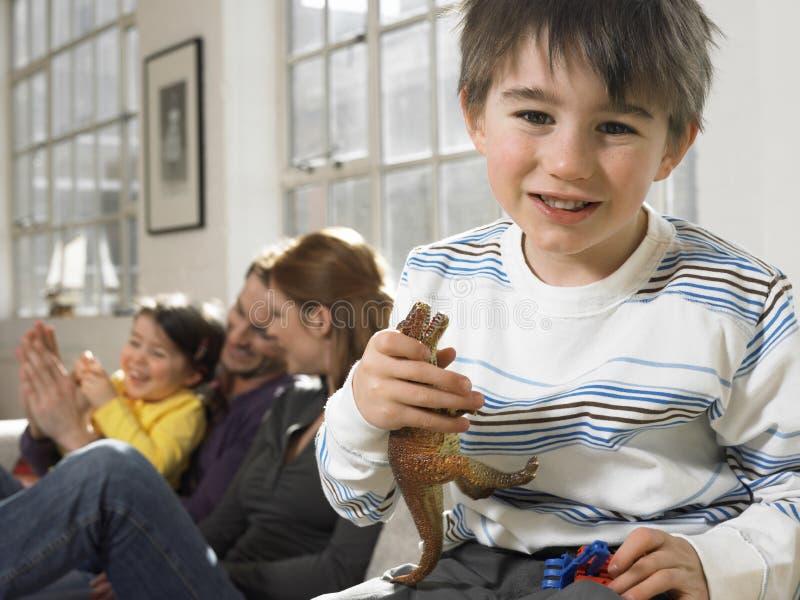 Мальчик держа животную игрушку при семья усмехаясь в предпосылке стоковые изображения rf