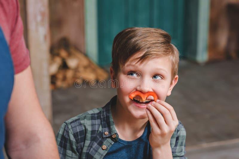Мальчик держа кусок перца как усик и смотря прочь стоковые фотографии rf