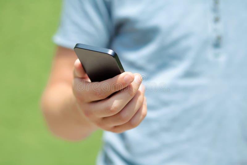 Download Мальчик держа телефон против зеленой стены Стоковое Фото - изображение насчитывающей связист, дело: 33738494