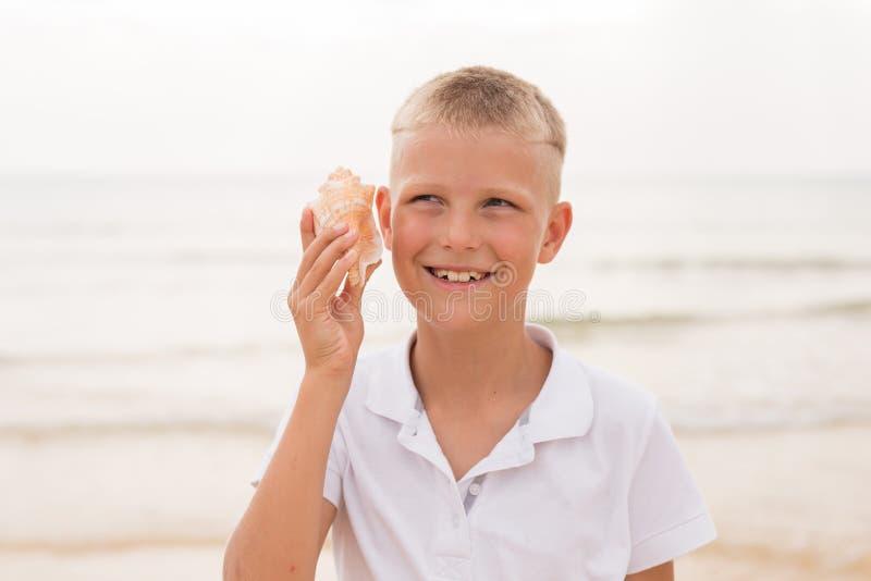 Мальчик держа seashell стоковое фото rf