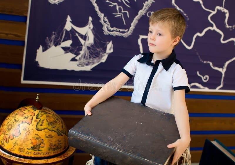 Мальчик держит книгу Комната с глобусом стоковое фото