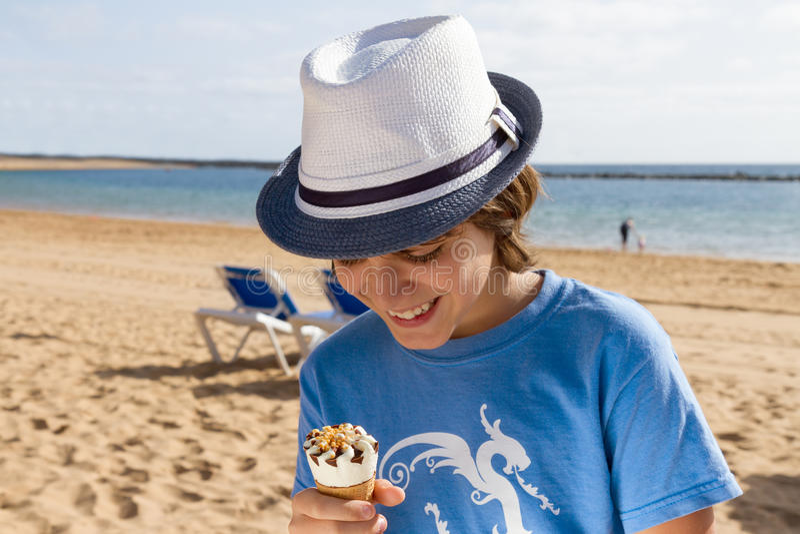 Мальчик есть мороженое на пляже стоковые фотографии rf