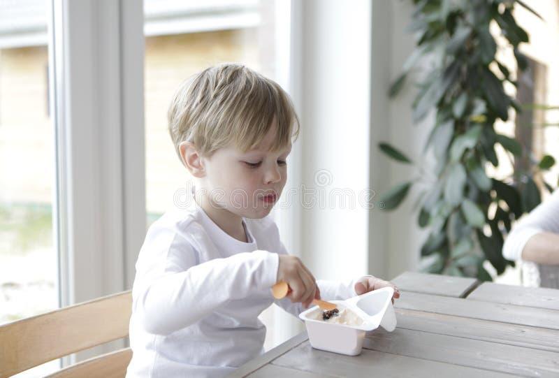 мальчик есть югурт стоковая фотография rf