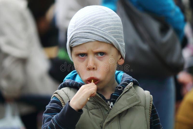 Мальчик ест леденец на палочке стоковые изображения