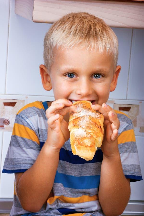 Мальчик ест крен стоковые изображения rf