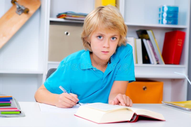 Мальчик делая домашнюю работу и читая книгу стоковое фото