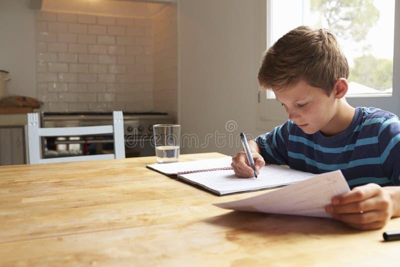 Мальчик делая домашнюю работу сидя на кухонном столе стоковое изображение rf