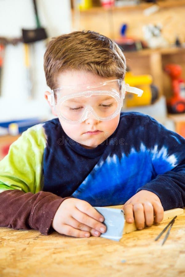 Мальчик зашкурить деревянный блок в мастерской стоковые изображения rf