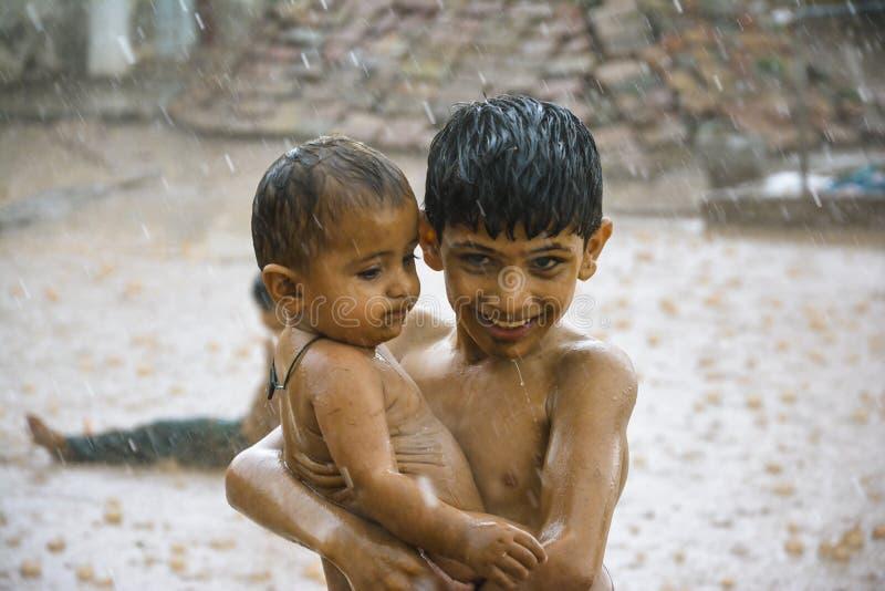 Мальчик защищая его маленького брата от проливного дождя стоковые фотографии rf